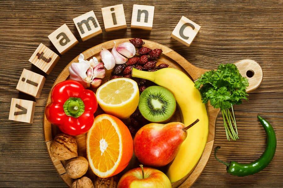 Scritta vitamina C attorno a un piatto pieno di alimenti ricchi di vitamina C