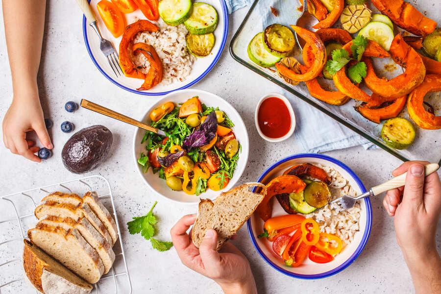 cibo sano su un tavolo con mani che mangiano