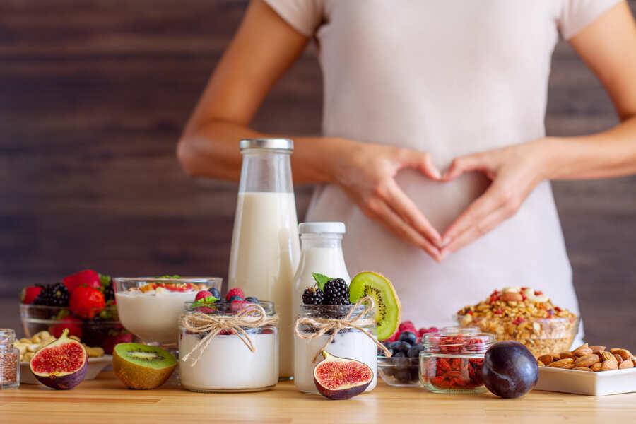 donna con le mani a cuore sullo sfondo di un tavolo con yogurt e frutta