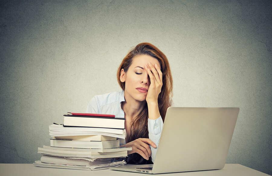 donna esausta con pc e libri