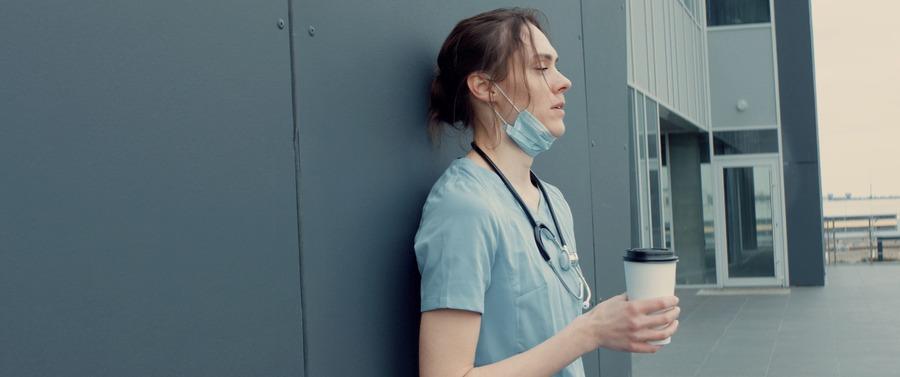 dottoressa o infermiera che beve un caffè stanca