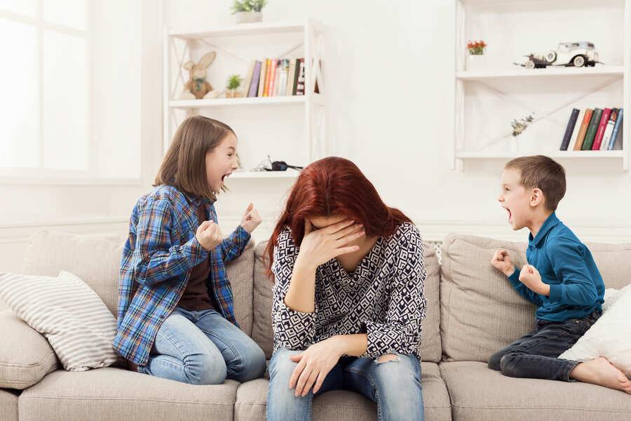 mamma sul divano stanca con i bambini che litigano