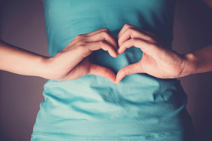 mani che formano un cuore con una ragazza con la maglia azzurra