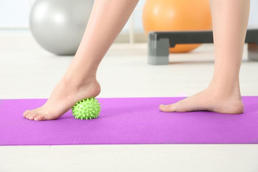 donna con un piede su una pallina