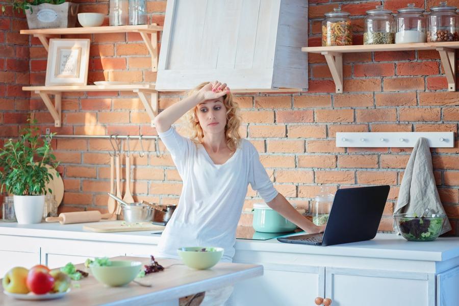 donna che guarda il tavolo della cucina sconsolata