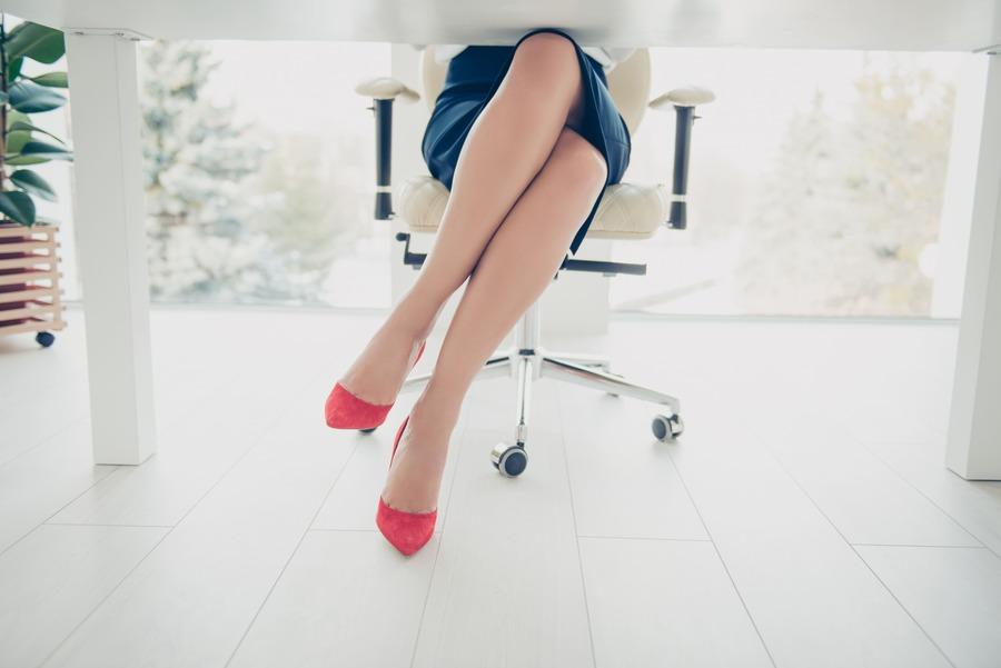 gambe di donna sotto una scrivania