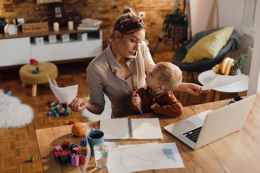 donna al telefono con un bambino in braccio