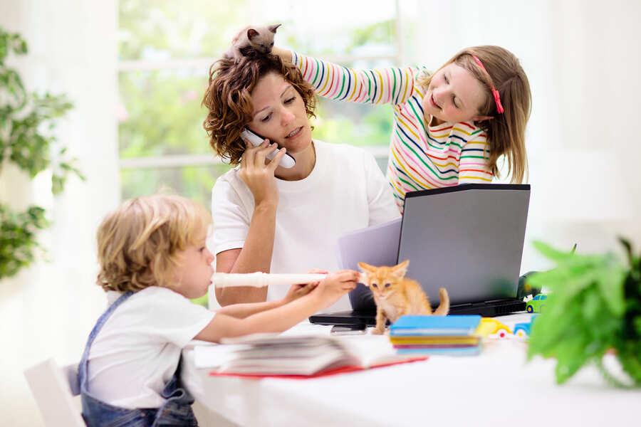 donna che lavora a casa mentre i bambini giocano