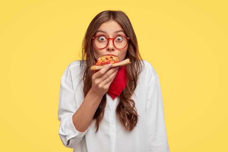 ragazza con gli occhiali che mangia la pizza