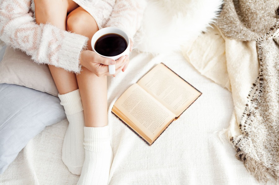 donna sul letto tra i cuscini con una tazza di caffè in mano e un libro di fianco