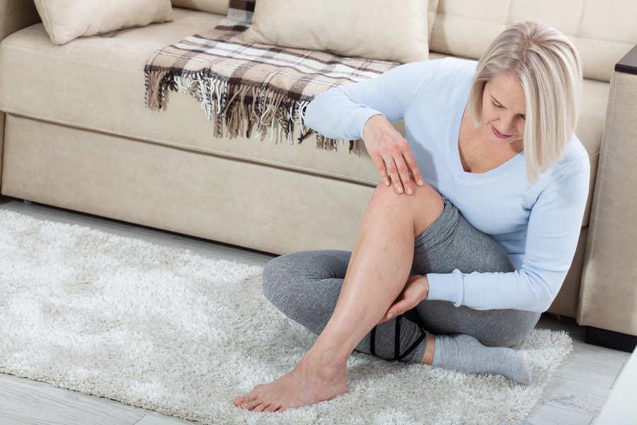 donna seduta a terra che osserva una sua gamba