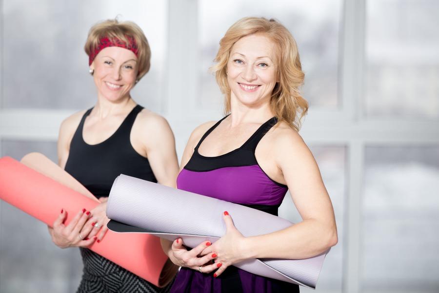 due donne con i tappetini da yoga