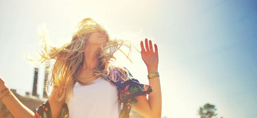 donna al sole che scuote i capelli
