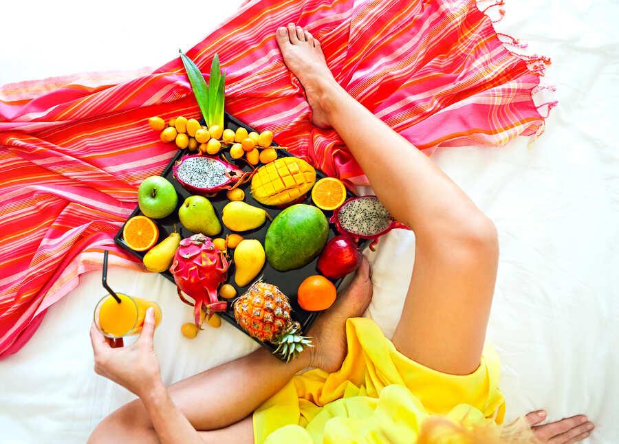 donna seduta con un vassoio di frutta