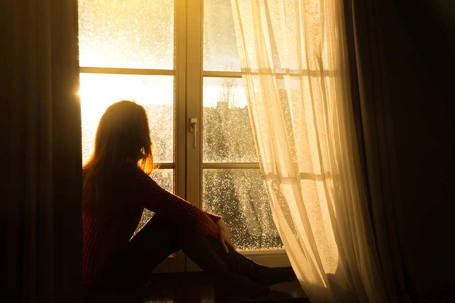 ragazza alla finestra che guarda la pioggia