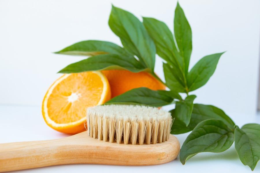 spazzola con le setole e arancia con foglie
